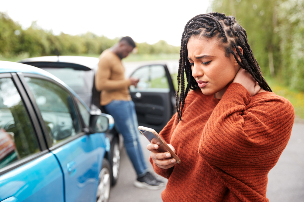 Woman who has been in a car accident and has neck pain calls someone on her cell phone.